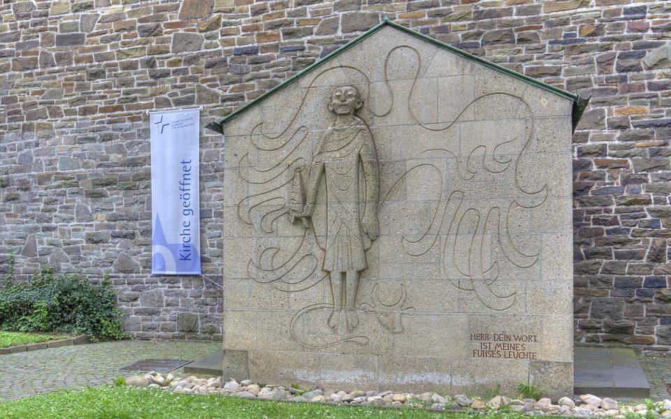 """Lukaskirche: Eingang mit Relief """"Lukas"""" und Transparent """"Kirche geöffnet"""""""