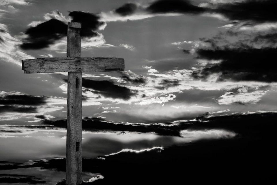 Kreuz vor Wolken, schwarzweiß.