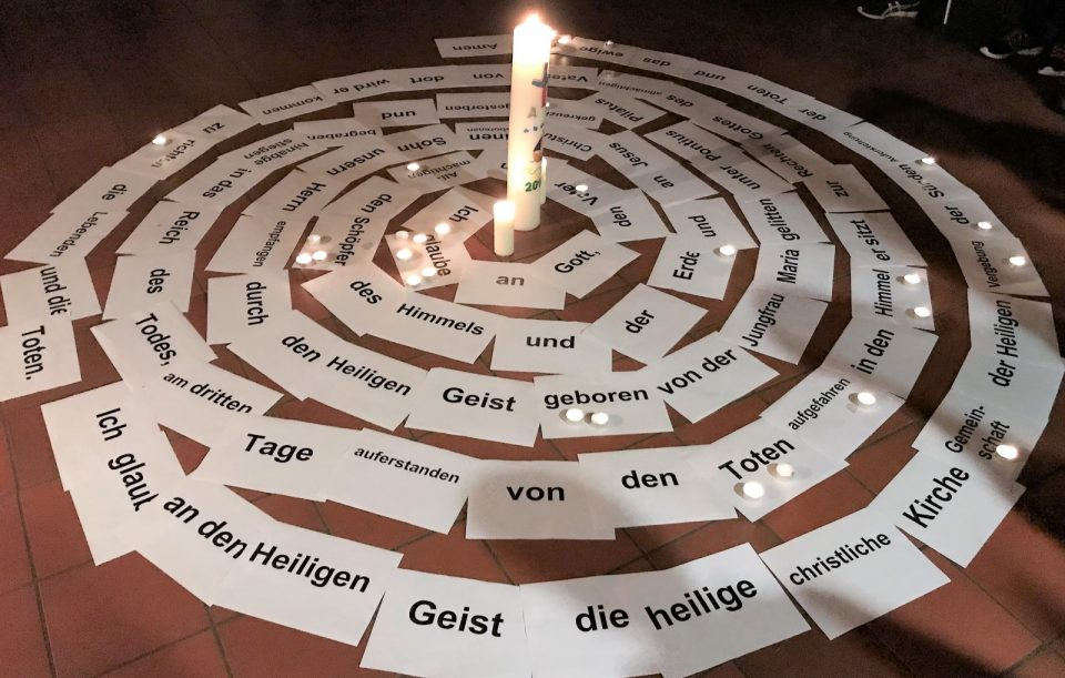 Szene aus dem KOnfirmandenunterricht: Glaubensbekenntnis (Zettel auf dem Boden), Kerze